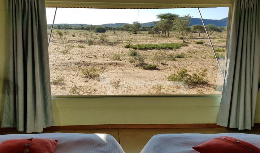 Blick vom Bett der Okonjima Lodge in das Reservat